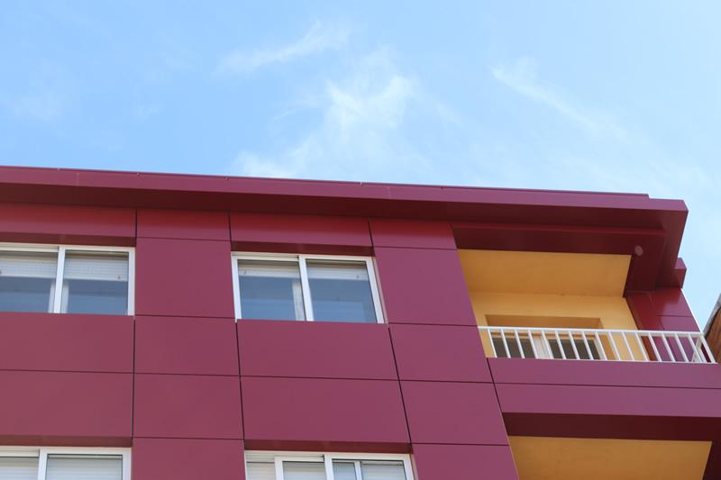 Imagen de detalle de la envolvente de edificio en A Estrada con colores potentes para este edificio de viviendas